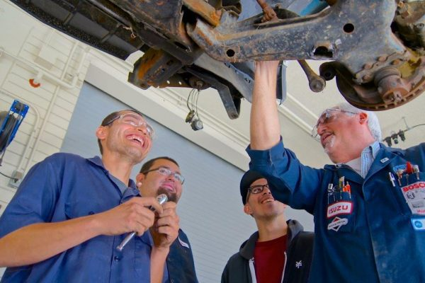 An Automotive Teacher Showing The Bottom Of The Car To Three Male Students.