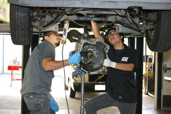 Two Male Automotive Students Working On A Car.