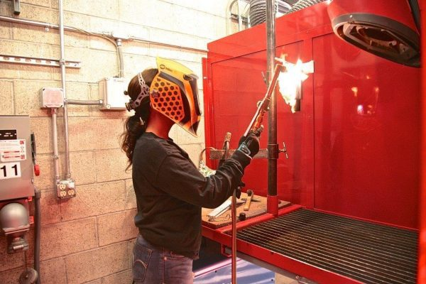 Female Holding A Welding Tool.