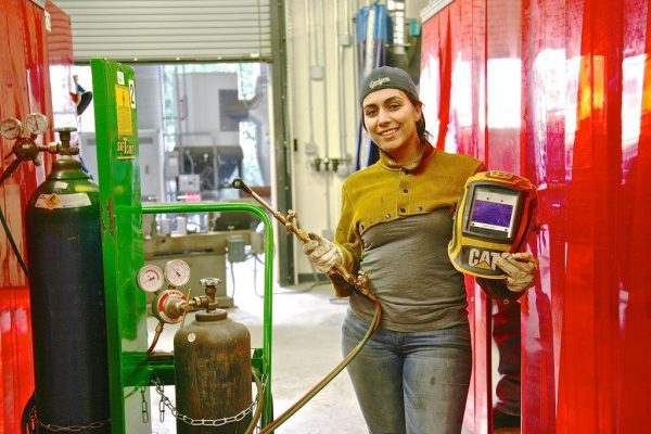 Female Holding A Welding Tool And Protection Gear.
